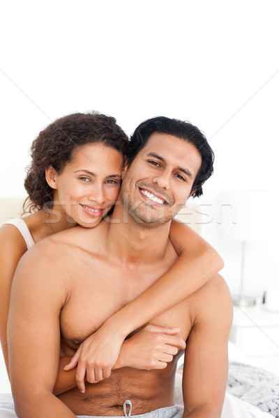 Portrait of a woman hugging her husband sitting together in the bedroom Stock photo © wavebreak_media