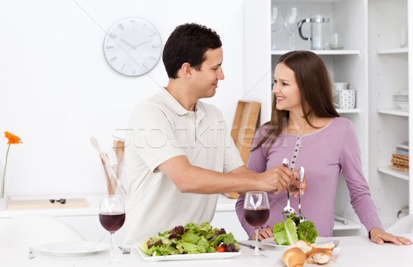 Attentive man serving salad to his girlfriend standing in the kitchen  Stock photo © wavebreak_media