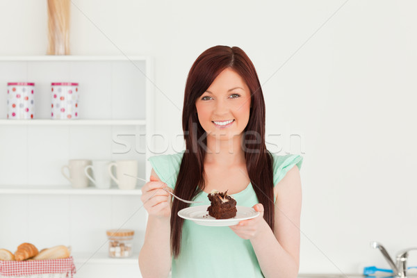 Good looking red-haired woman eating some cake in the kitchen in her appartment Stock photo © wavebreak_media