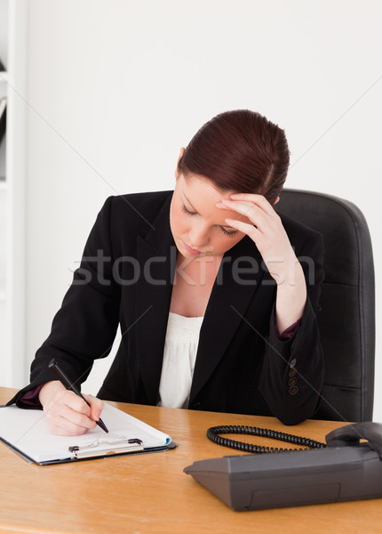 Depressed beautiful red-haired woman in suit writing on a notepad while sitting in an office Stock photo © wavebreak_media