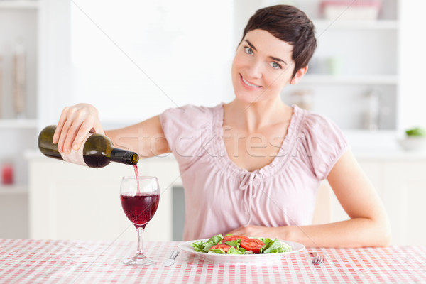 Woman pouring redwine in a glass in a kitchen Stock photo © wavebreak_media