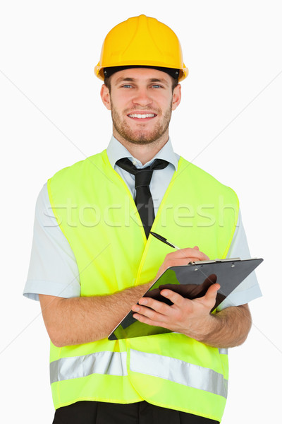 Smiling young foreman with his clipboard against a white background Stock photo © wavebreak_media