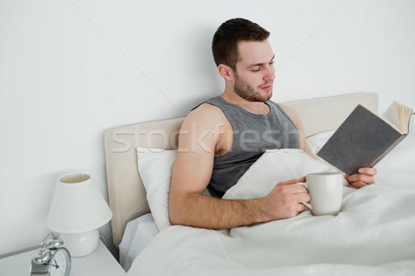 笑みを浮かべて 男 読む 茶 ベッド 幸せ ストックフォト © wavebreak_media
