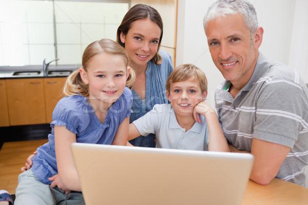 Charming family using a laptop in their kitchen Stock photo © wavebreak_media