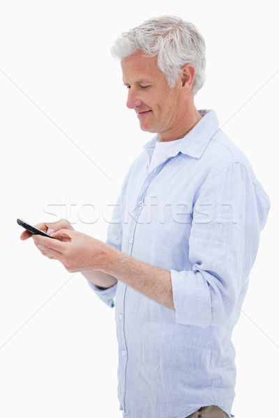 Portrait of a man using his mobile phone against a white background Stock photo © wavebreak_media