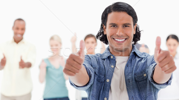 Close-up of a man with his thumbs-up with people behind against white background Stock photo © wavebreak_media