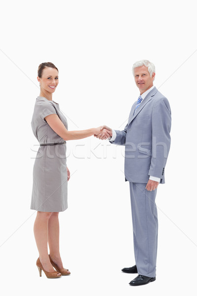 White hair man face to face and shaking hands with a woman against white background Stock photo © wavebreak_media