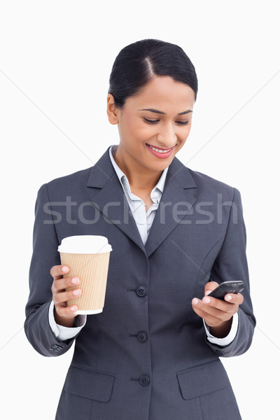 Close up of saleswoman with paper cup reading text message against a white background Stock photo © wavebreak_media