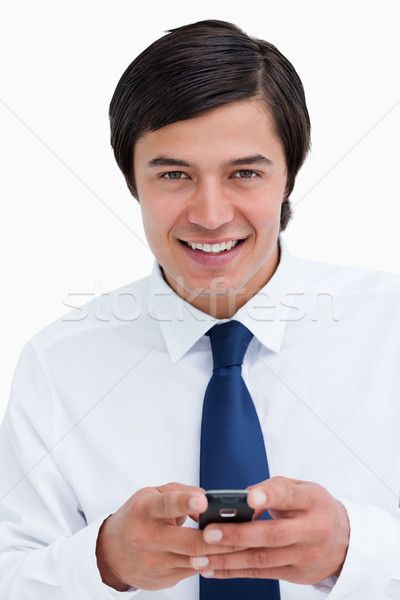 Close up of smiling tradesman holding his cellphone against a white background Stock photo © wavebreak_media