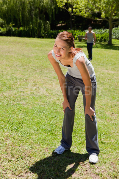 Woman smiling as she bends over recovering while a man is walking towards her in the background Stock photo © wavebreak_media