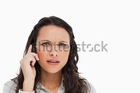 Portrait of a brunette grimacing while making a call against white background Stock photo © wavebreak_media