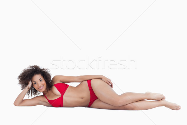 Smiling young brunette woman lying down while looking straight at the camera Stock photo © wavebreak_media
