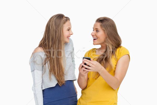 Two happy young women looking a smartphone against white background Stock photo © wavebreak_media