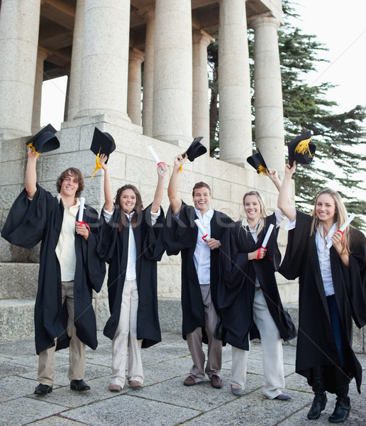 Five happy grad students raising their hats in front of the university Stock photo © wavebreak_media