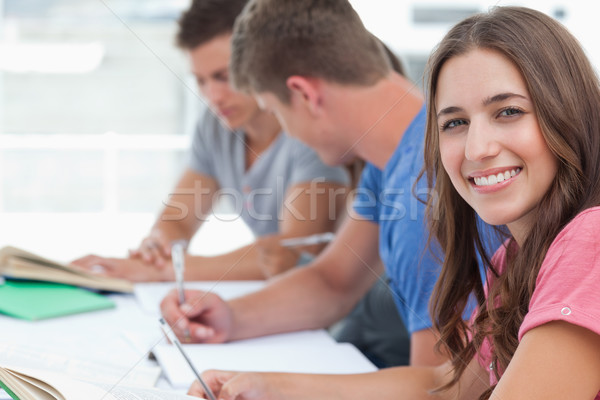 A woman smiling at the camera while her friends sit beside her looking at the homework they have Stock photo © wavebreak_media