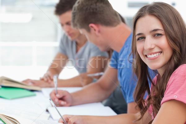 Mujer sonriente cámara amigos sentarse mirando Foto stock © wavebreak_media