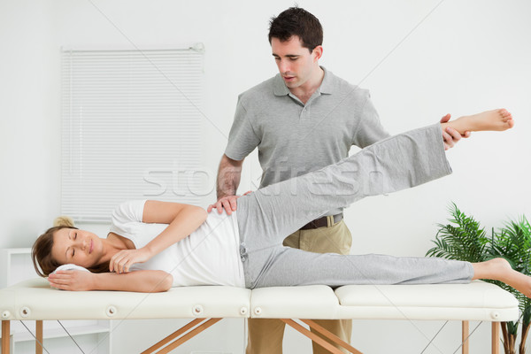 Serious practitioner rising the leg of his patient in his room Stock photo © wavebreak_media