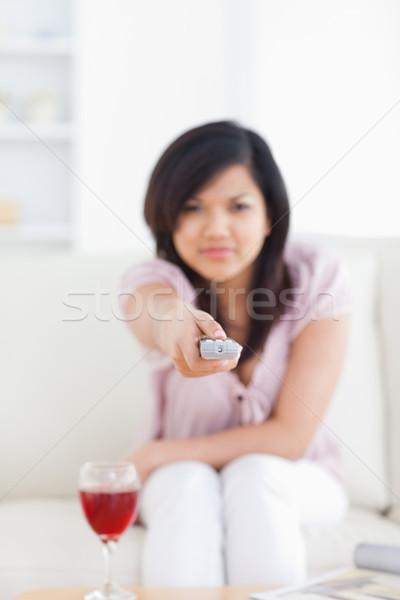 Offuscata donna televisione remote soggiorno Foto d'archivio © wavebreak_media
