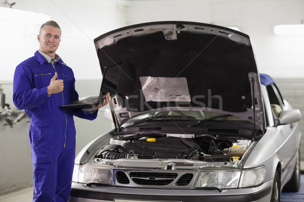 Mechanic holding a computer with thumb up in a garage Stock photo © wavebreak_media