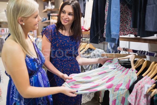 Two woman talking beside clothes rail in shopping mall Stock photo © wavebreak_media