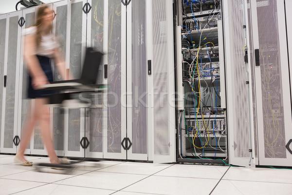 Woman pushing computer through data center beside the servers Stock photo © wavebreak_media