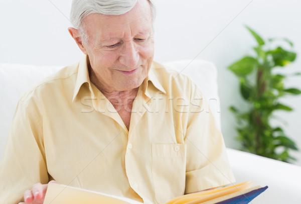Elderly smiling man watching his album Stock photo © wavebreak_media