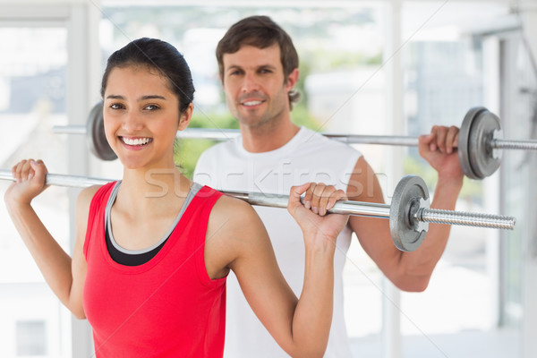 Fit young couple lifting barbells in gym Stock photo © wavebreak_media