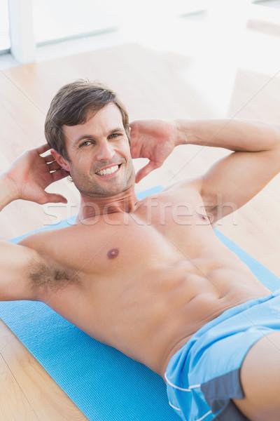 Uśmiechnięty półnagi człowiek siedzieć fitness studio Zdjęcia stock © wavebreak_media