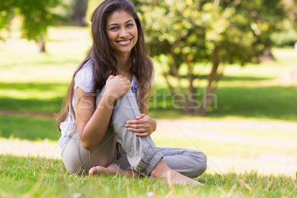 Full length portrait of smiling woman sitting in park Stock photo © wavebreak_media