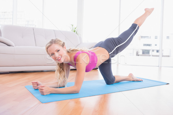 Toned blonde doing pilates on exercise mat smiling at camera Stock photo © wavebreak_media