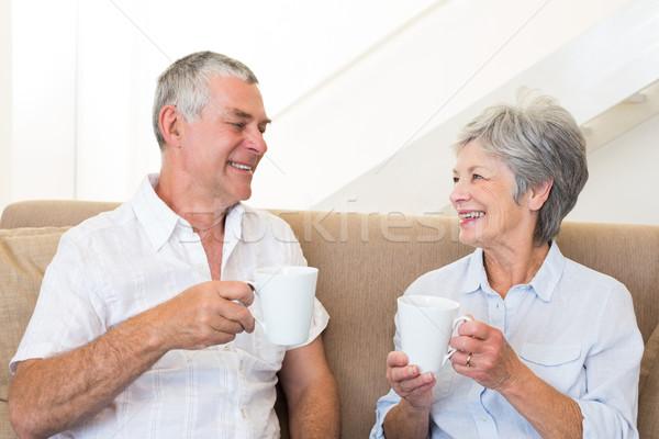Senior couple sitting on couch drinking coffee Stock photo © wavebreak_media