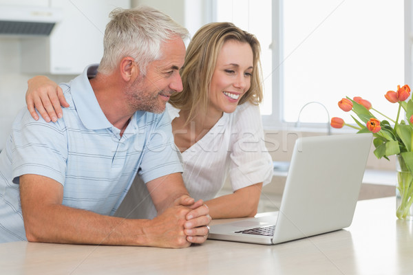 Cheerful couple using laptop together at the worktop Stock photo © wavebreak_media