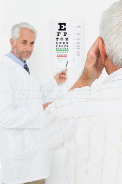 Kinderarts oogarts senior patiënt wijzend oog Stockfoto © wavebreak_media