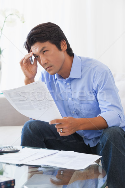 Serious man sitting on couch paying his bills Stock photo © wavebreak_media