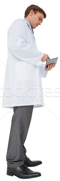 Young doctor in lab coat using tablet pc Stock photo © wavebreak_media