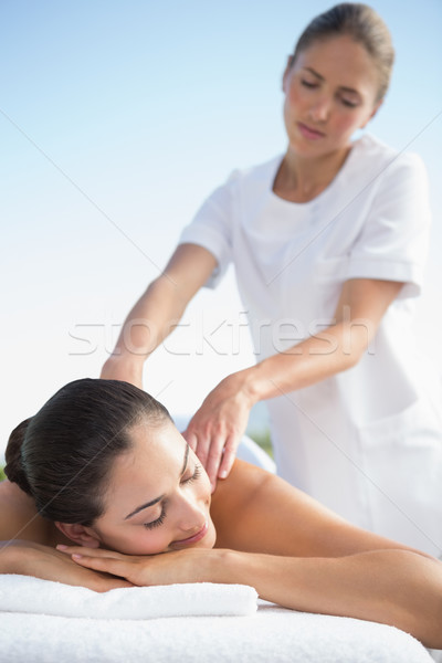 Calm brunette enjoying a massage poolside Stock photo © wavebreak_media