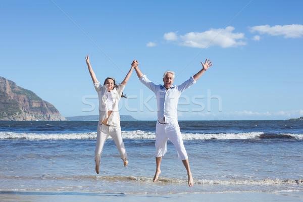 Feliz casal saltando para cima descalço praia Foto stock © wavebreak_media