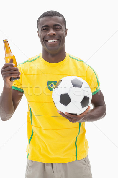 Happy brazilian football fan in yellow holding beer and ball Stock photo © wavebreak_media