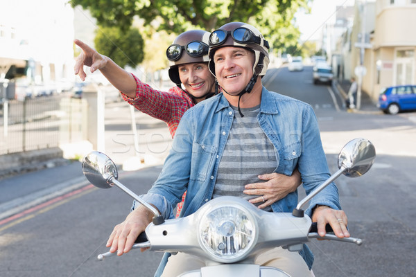 Happy mature couple riding a scooter in the city Stock photo © wavebreak_media