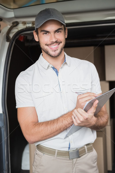 Delivery driver smiling at camera beside his van Stock photo © wavebreak_media