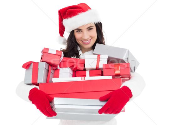Smiling brunette in santa hat holding stack of presents Stock photo © wavebreak_media