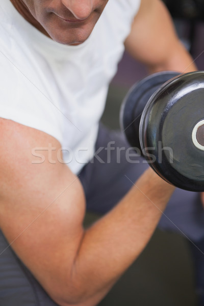 Fit man lifting dumbbells sitting on the bench Stock photo © wavebreak_media