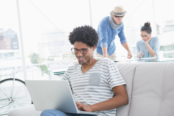 Stock photo: Young creative man using laptop on couch