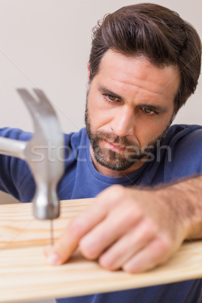 Casual man hammering nail in plank Stock photo © wavebreak_media