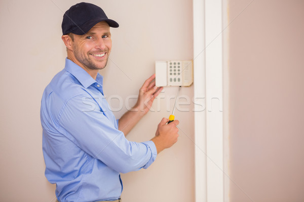 Smiling handyman fixing an alarm system Stock photo © wavebreak_media