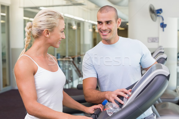 Trainer assisting woman with treadmill screen options at gym Stock photo © wavebreak_media