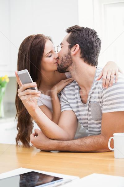 Young man using smartphone while girlfriend kisses him Stock photo © wavebreak_media