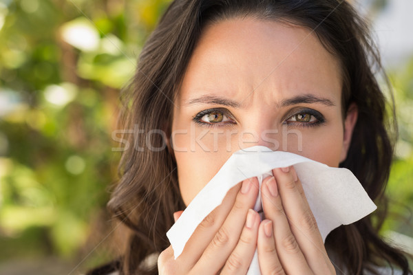 Pretty brunette blowing her nose Stock photo © wavebreak_media