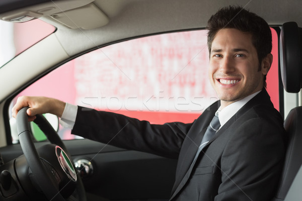Smiling businessman at the wheel sitting in a car for sale Stock photo © wavebreak_media