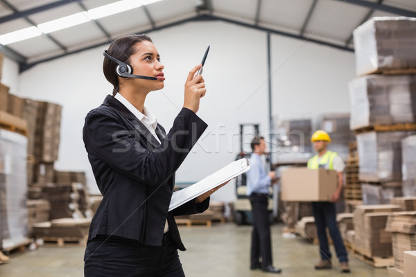 Warehouse manager wearing headset checking inventory  Stock photo © wavebreak_media